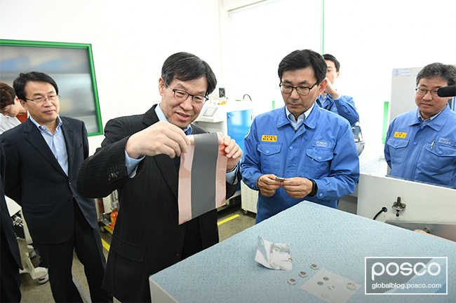 POSCO CEO Ohjoon Kwon is seen examining the anode plate coating used in secondary batteries.