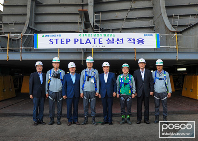 Employees of the two companies are posing for a picture in front of the hull that was assembled using STEP.