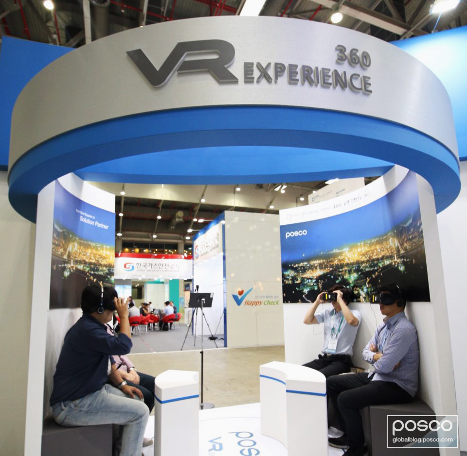 Visitors are sitting at POSCO's booth wearing headsets to watch VR video.