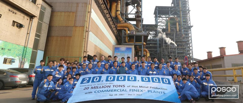 POSCO employees gather outside the FINEX technology production facilities for a photo.